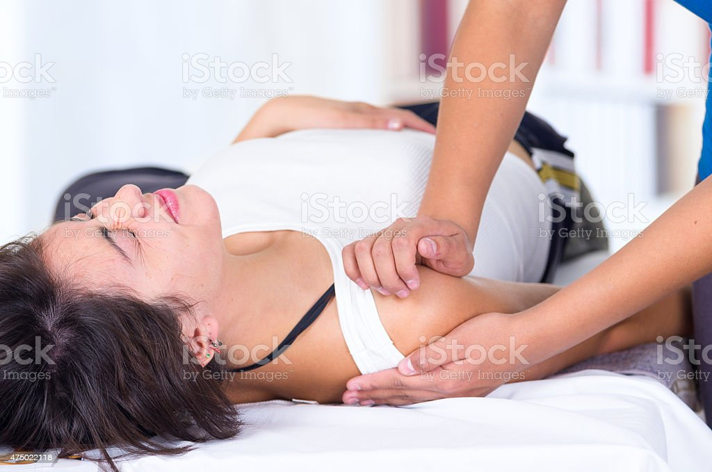 woman in pain lying while getting a shoulder massage concept stock photo