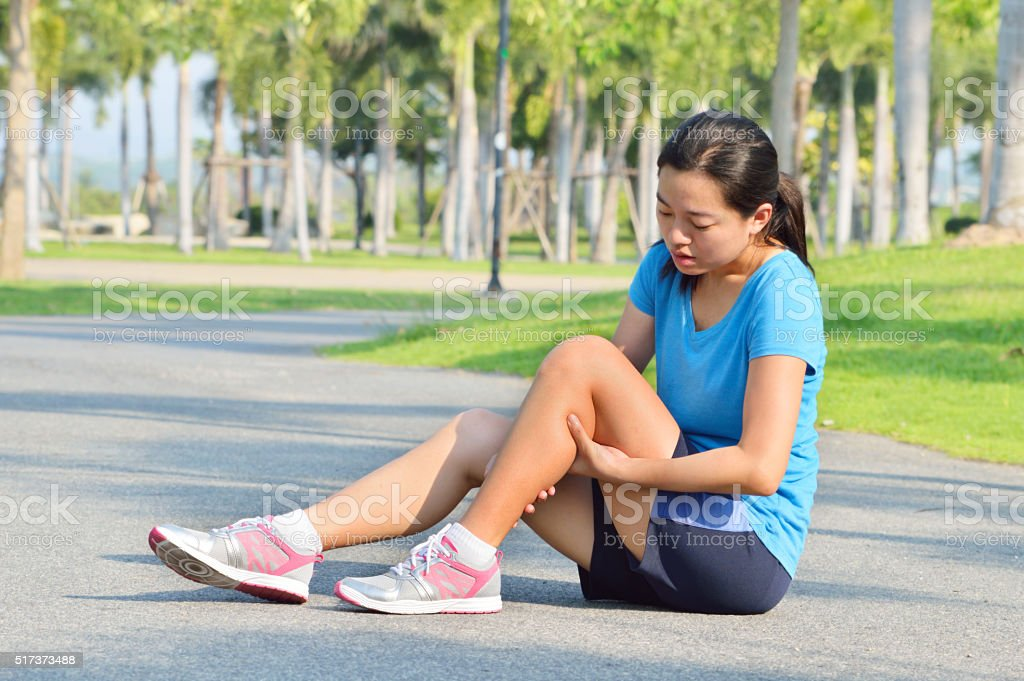 Woman in pain while running in park stock photo