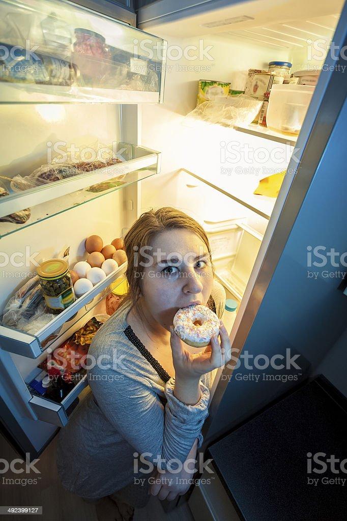 woman in pajamas eating donut next to refrigerator stock photo