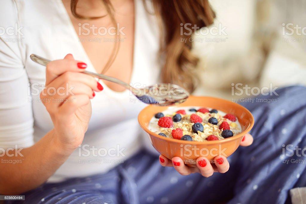 woman in pajamas in bedroom eating muesli with berries stock photo