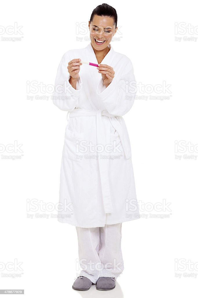 woman in pajamas with positive pregnancy test stock photo