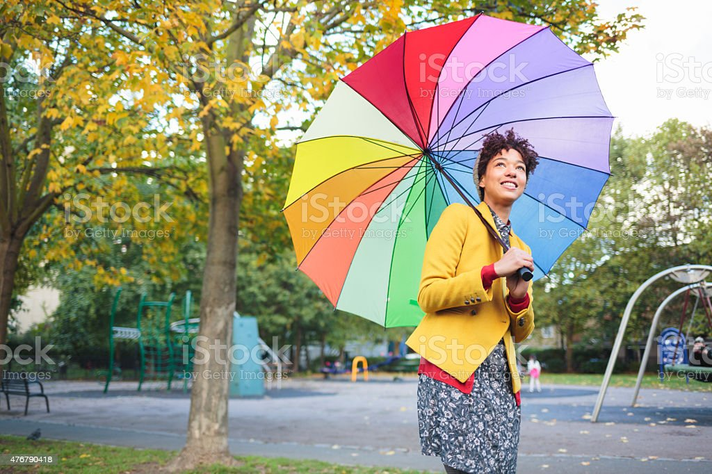 Woman in park with colorful umbrella. stock photo