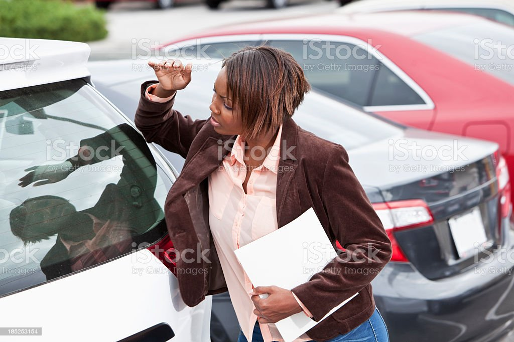 Woman in parking lot, looking inside car royalty-free stock photo