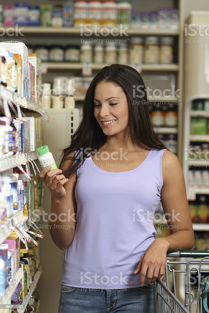 Woman in Pharmacy Looks at Pills Vertical royalty-free stock photo