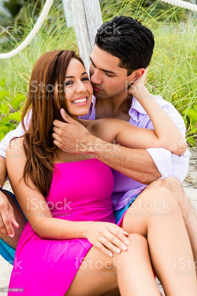 Woman in pink embracing love while being kissed by boyfriend stock photo