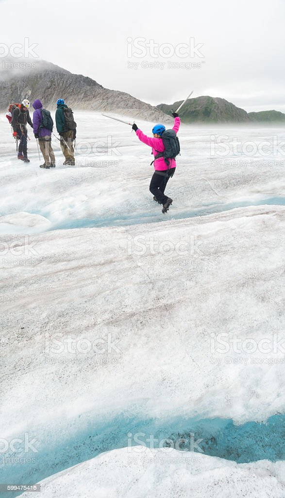 Woman in pink fleece jumps over ice stock photo