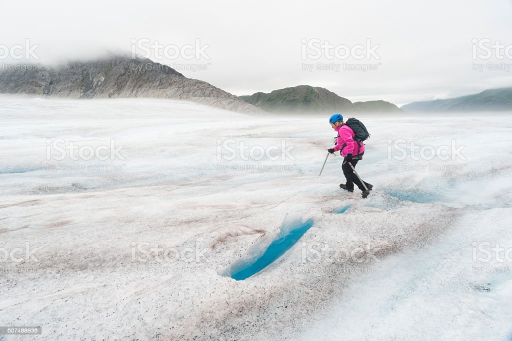 Woman in pink hikes across glacier stock photo