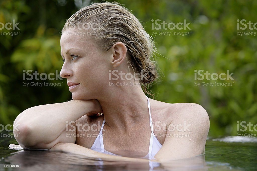woman in pool surrounded by trees stock photo