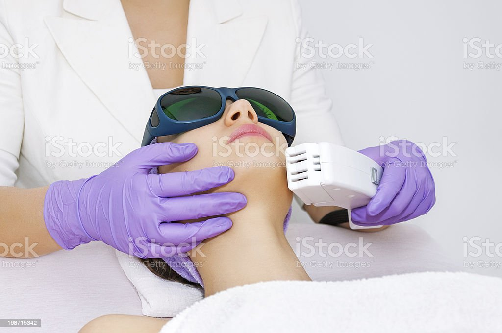 Woman in protective glasses receiving laser hair removal royalty-free stock photo