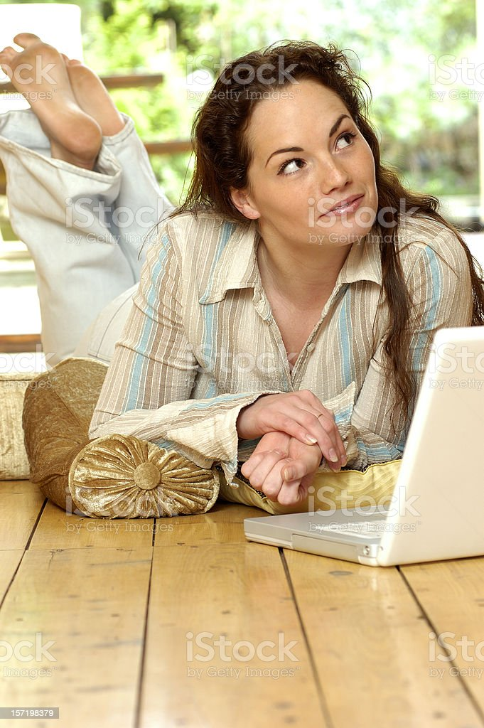 woman in pyjamas on floor with laptop royalty-free stock photo