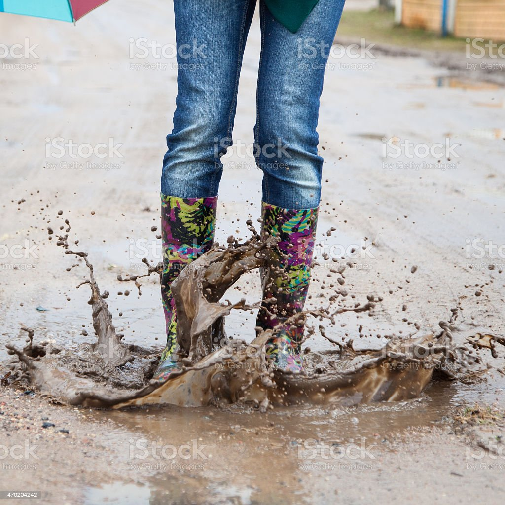 Woman in rain boots jumps stock photo