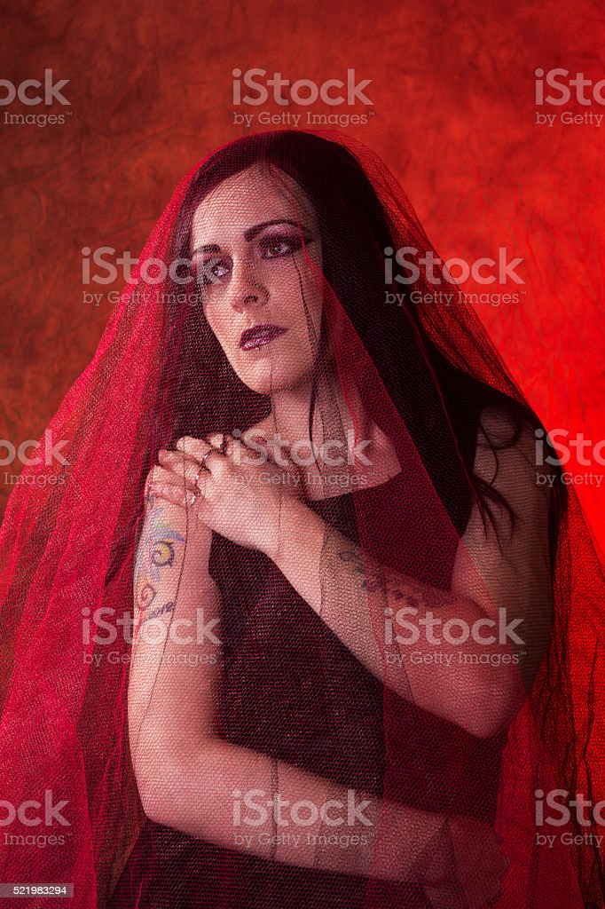 Woman in red and black veil, hands on head. stock photo