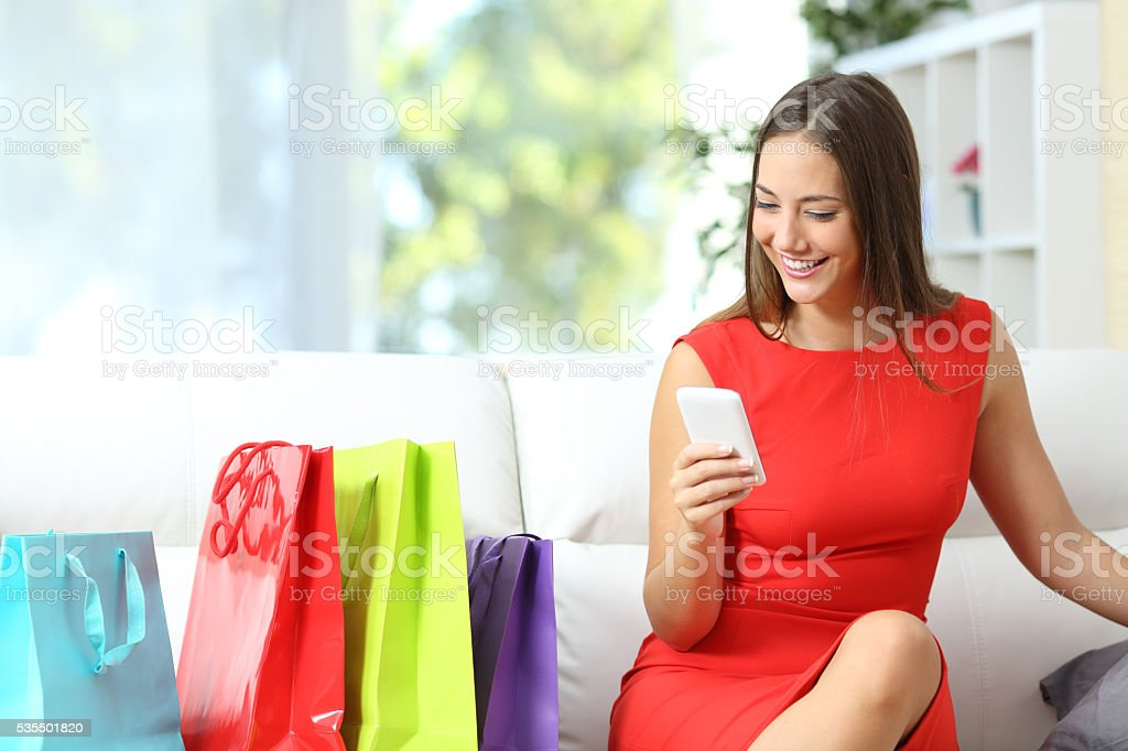 Woman in red buying with a smart phone stock photo