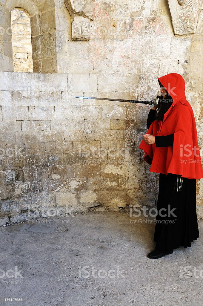 woman in red cape defending with sword stock photo