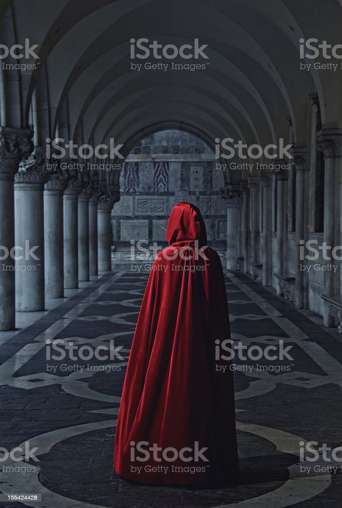Woman in red cloak walking away stock photo