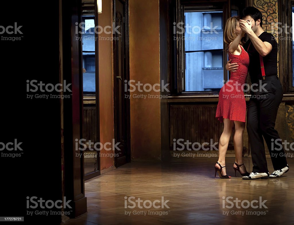 Woman in red dress and a man passionately doing the tango stock photo