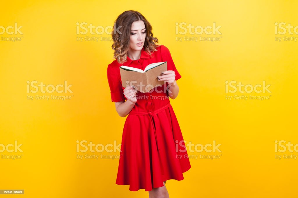 woman in red dress is holding a book stock photo