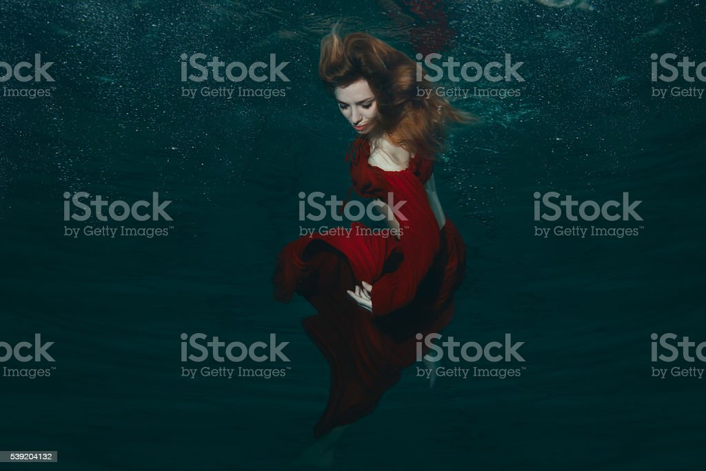 Woman in red dress underwater. stock photo