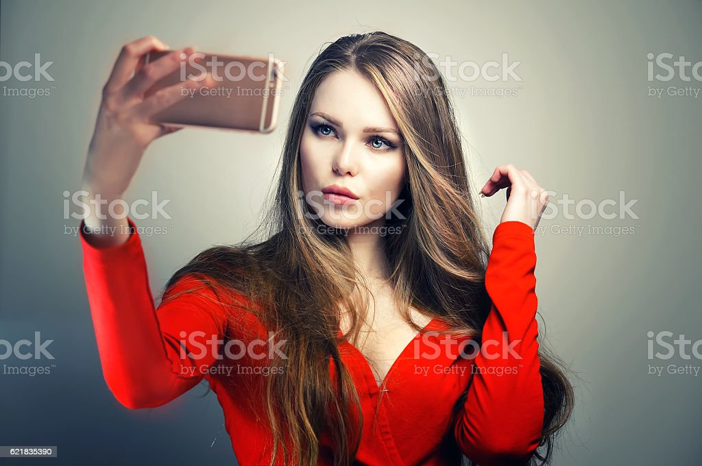 Woman in red dress with perfect cute face taking selfie. stock photo