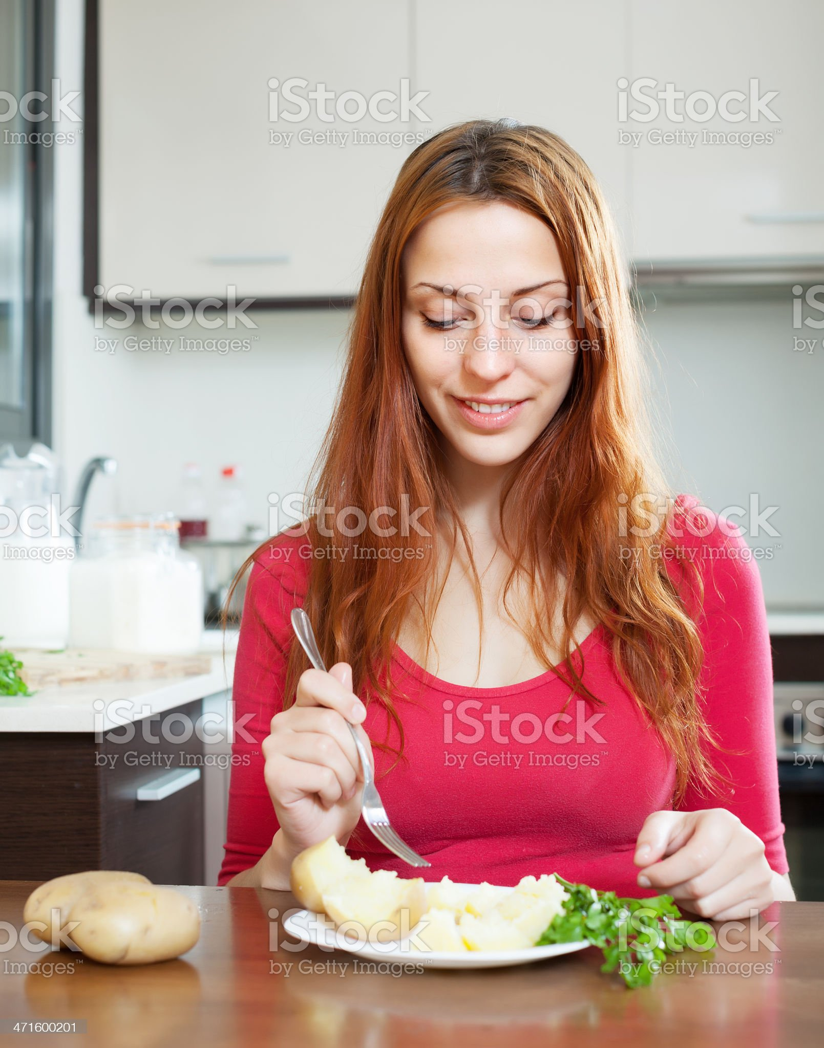 woman in red eating  potatoes royalty-free stock photo
