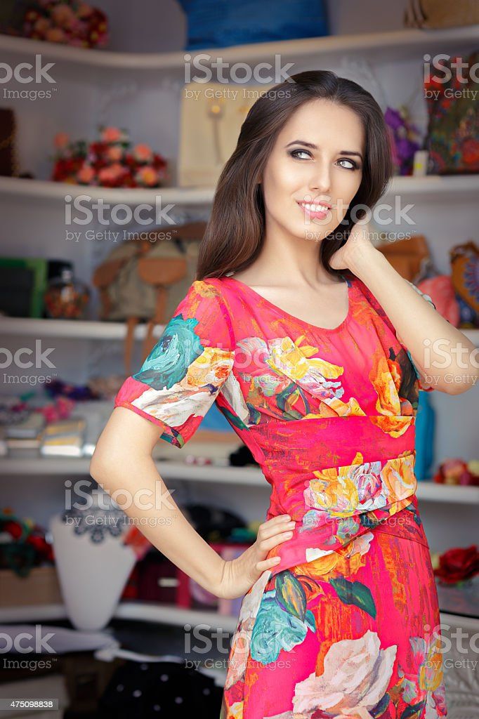 Woman in Red Floral Dress in Fashion Store stock photo