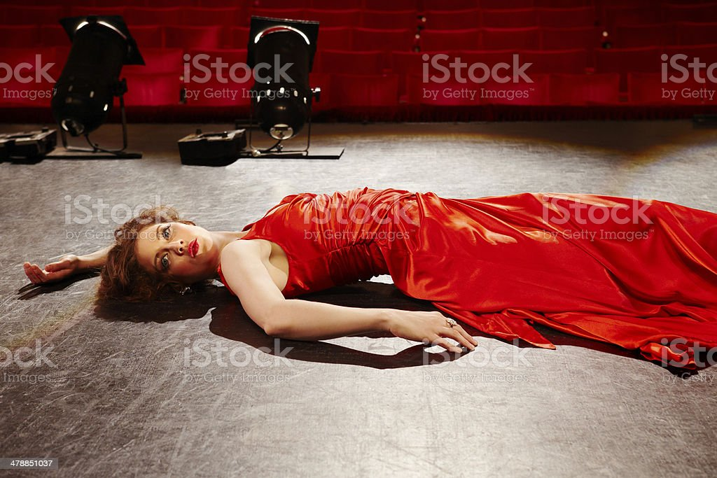 Woman In Red Gown Lying On Stage stock photo