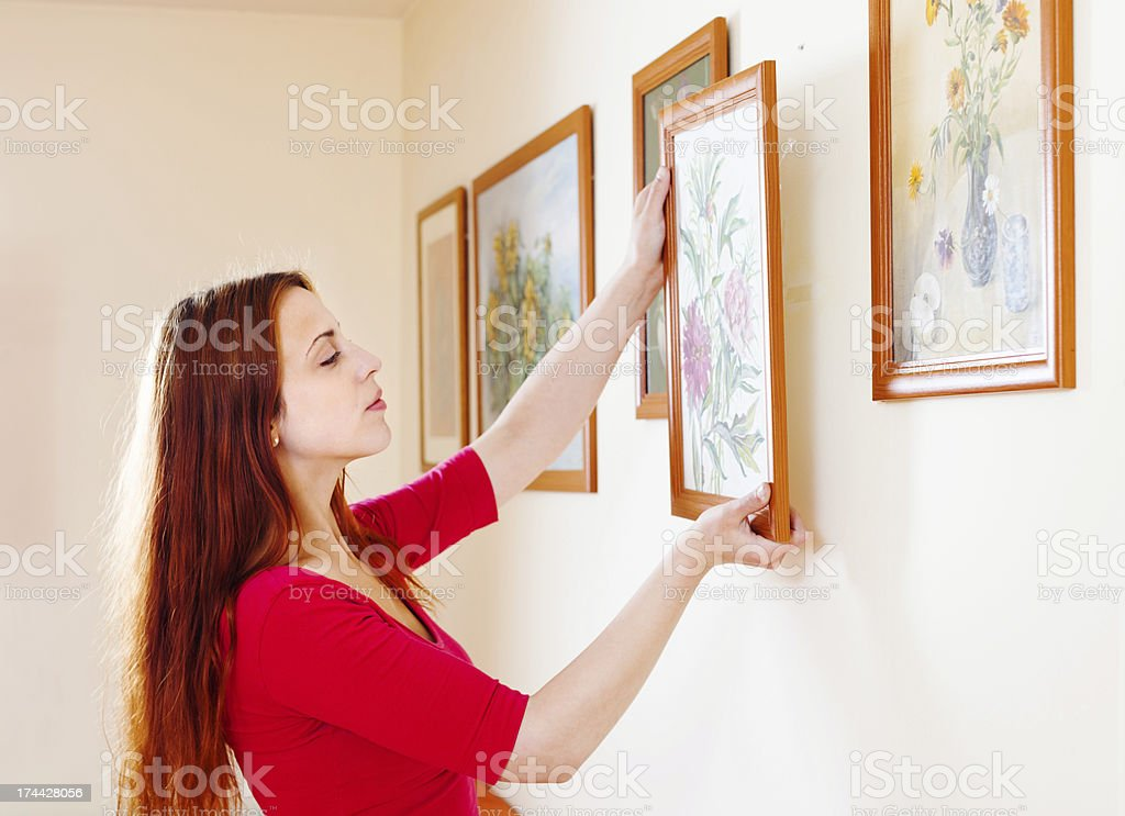 woman in red hanging the art pictures stock photo