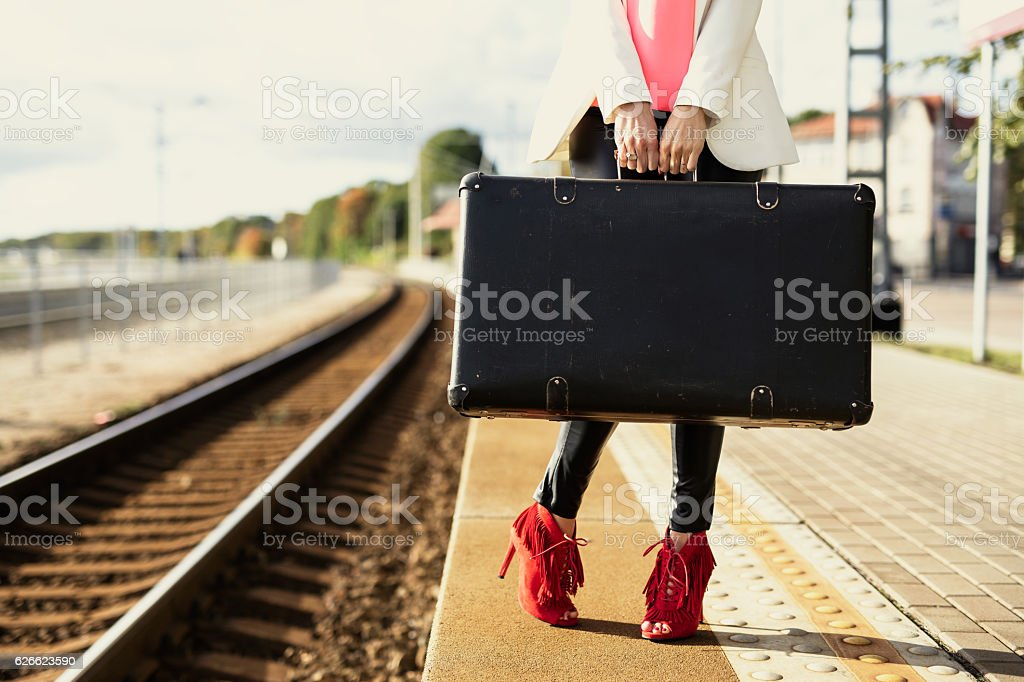 Woman in red heels waiting in train station with  suitcase stock photo