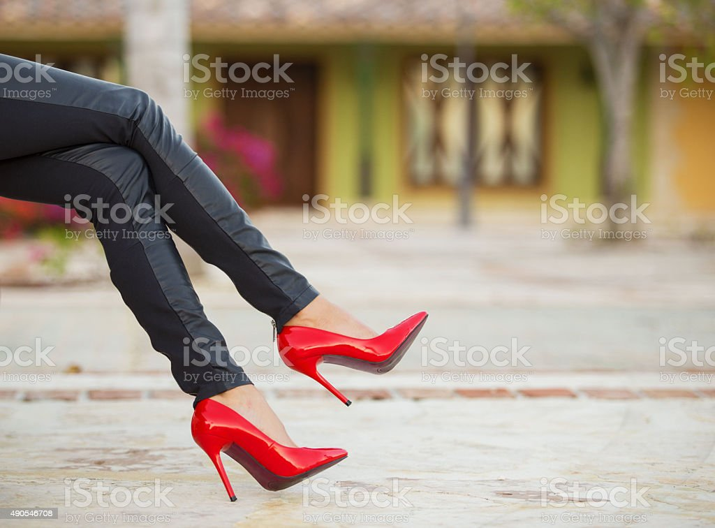 Woman in red high heel shoes sitting on bench stock photo