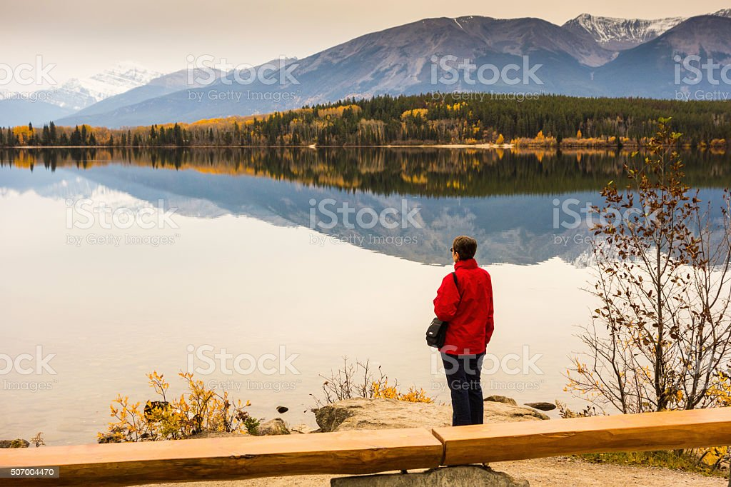 Woman in Red Jacket Views Mountain Lake stock photo
