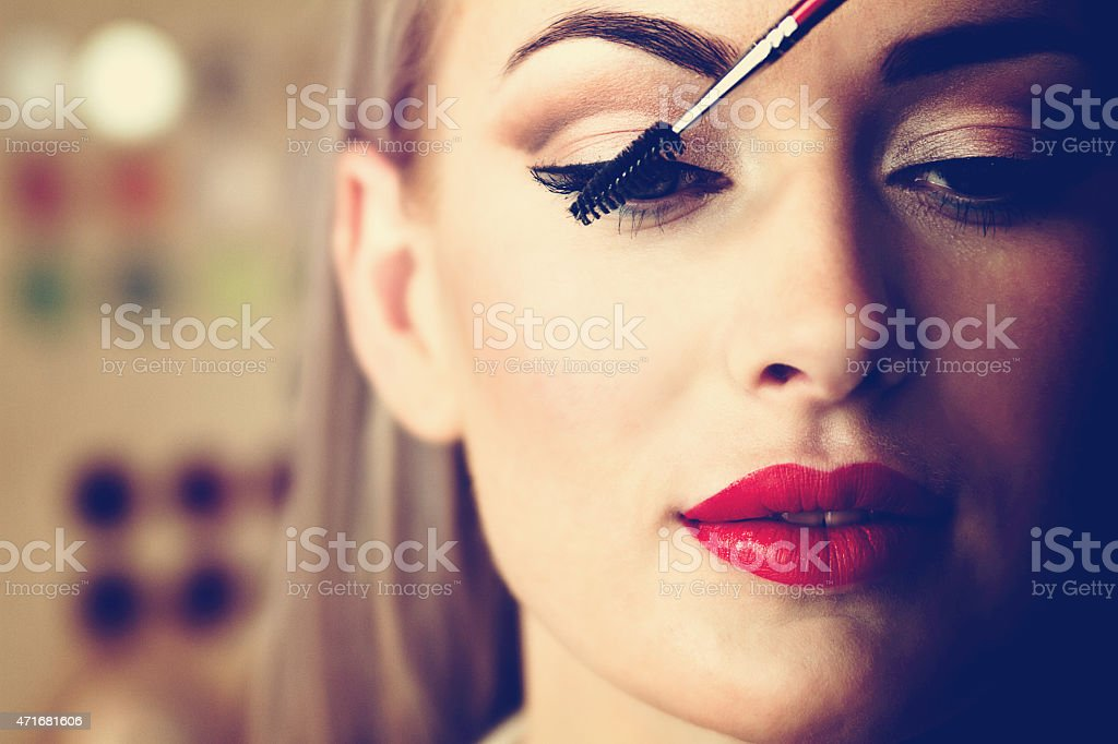 A woman in red lipstick applying mascara stock photo