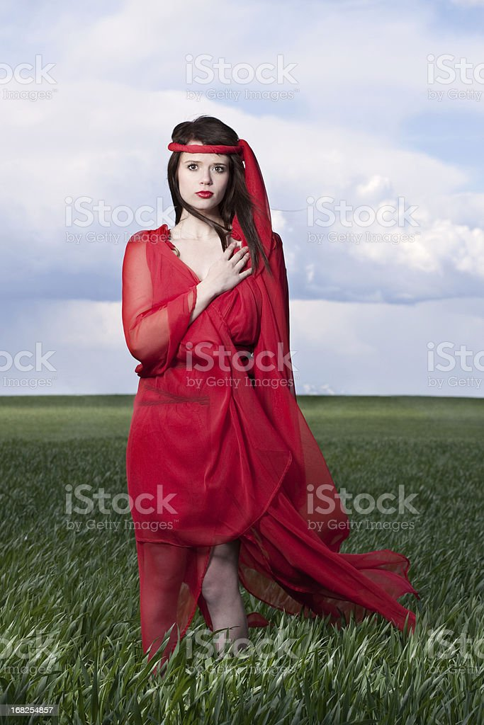 Woman in Red Outdoors with Hand Over Heart stock photo