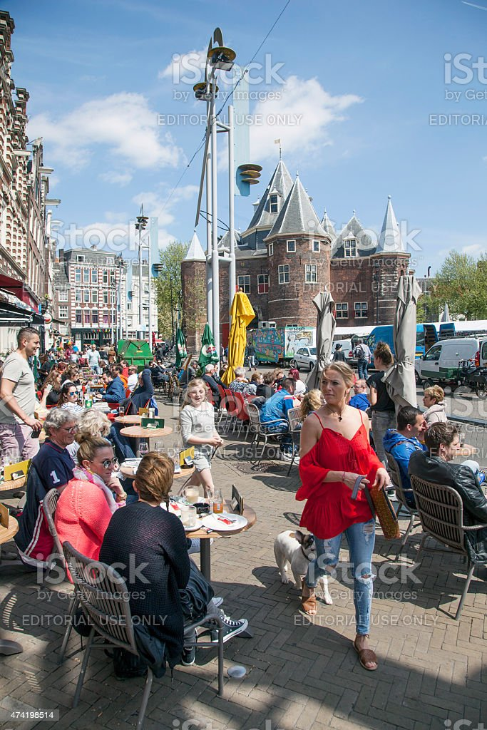 woman in red passes many people on nieuwmarkt amsterdam stock photo