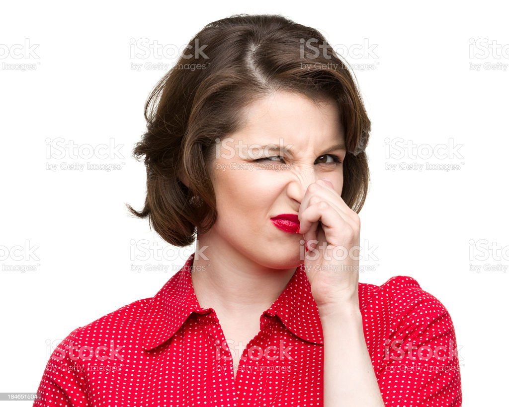 Woman in red pinching her nose showing dislike stock photo