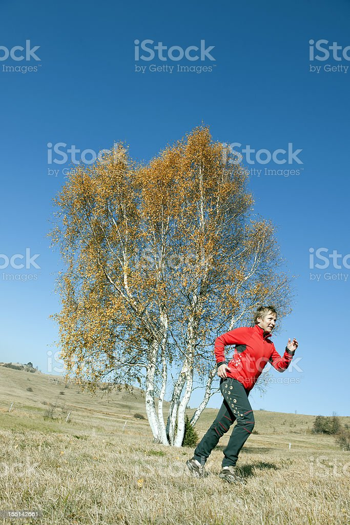 Woman in Red Running by Autumnal Birch royalty-free stock photo