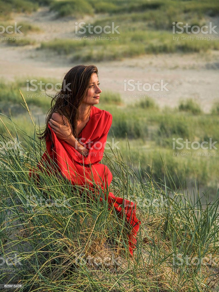 Woman in red scarf sitting on sand dune stock photo
