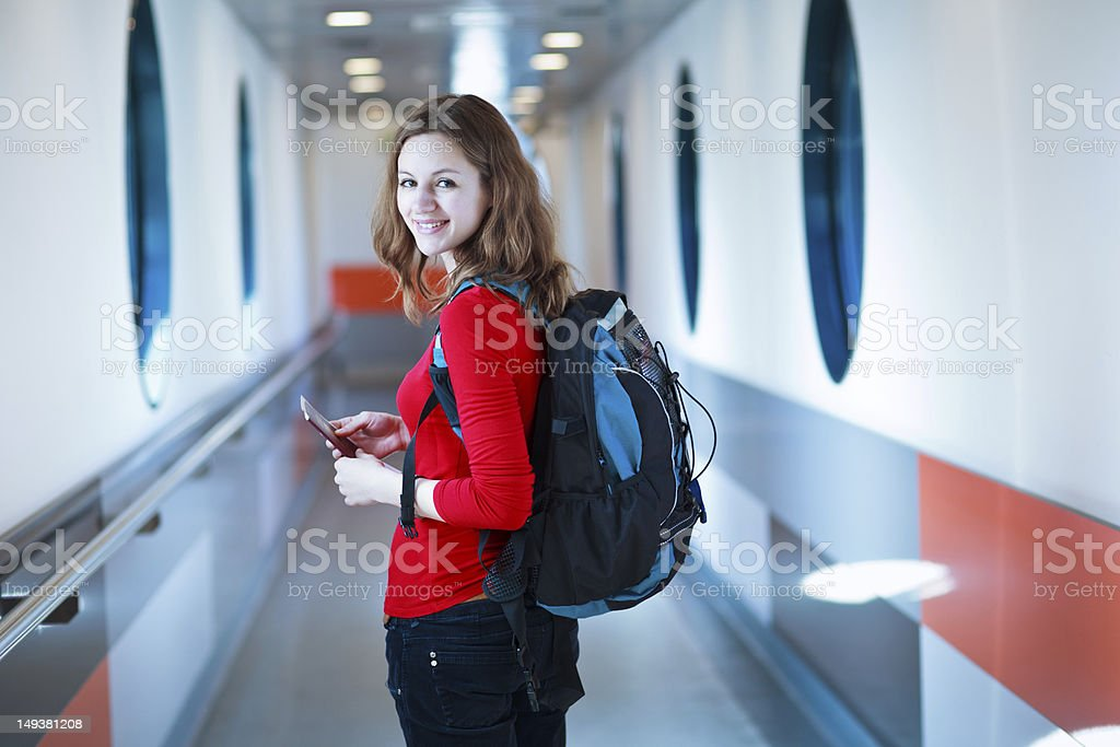 Woman in red shirt with book bag boarding a flight stock photo