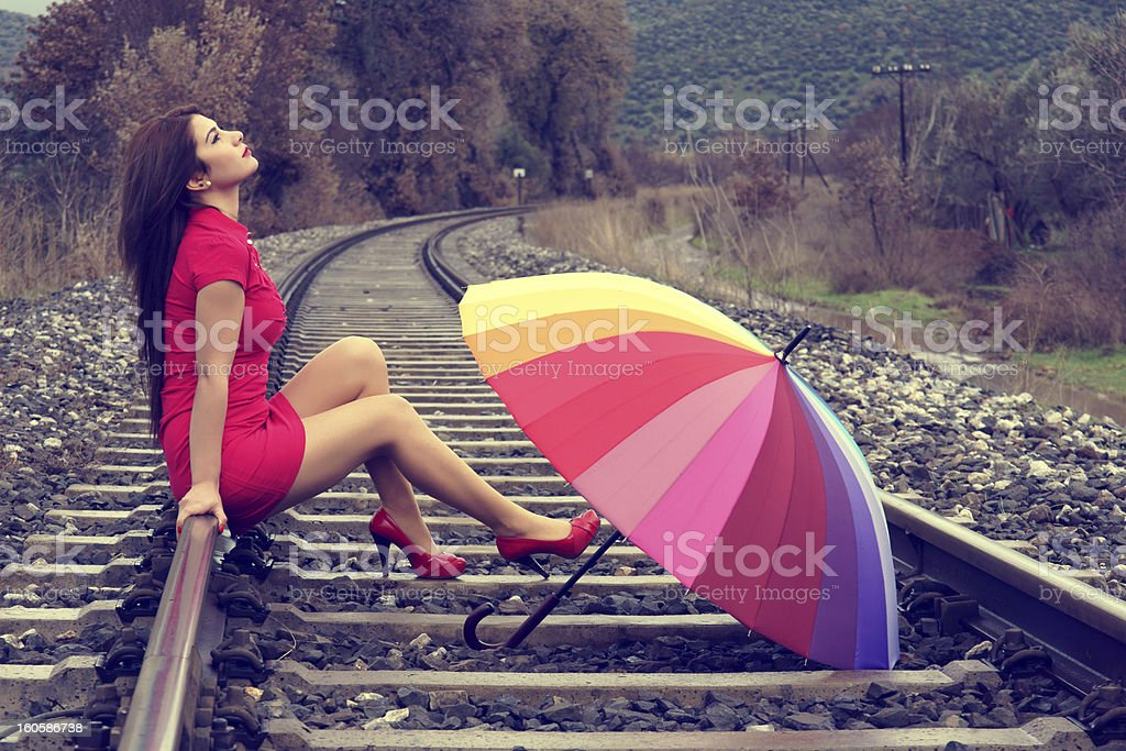 Woman in red sitting on rails royalty-free stock photo