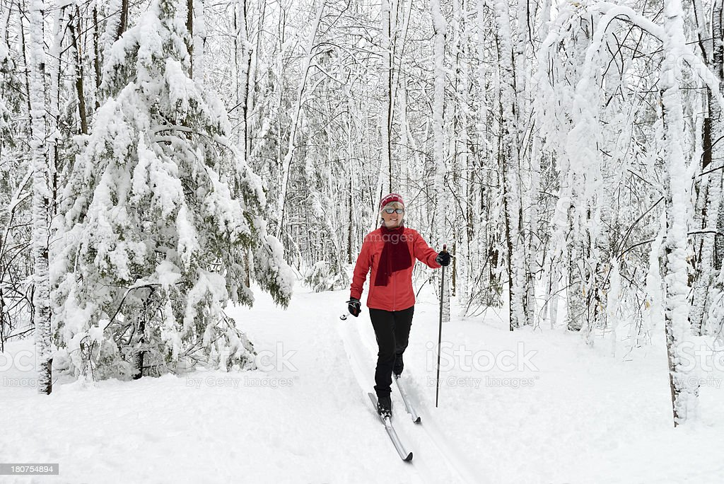 Woman in red skiing through snowy forest royalty-free stock photo