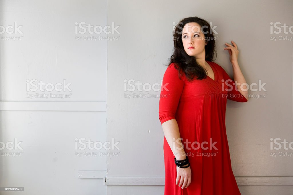 Woman in red standing against a wall stock photo