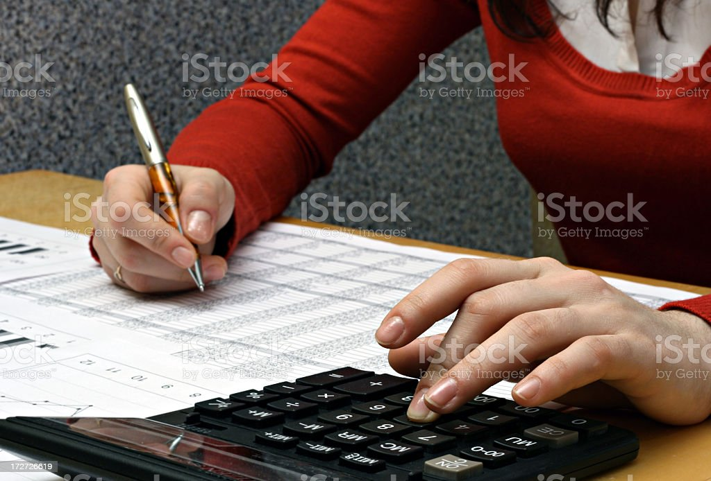 Woman in red using pen and calculator on financial documents royalty-free stock photo