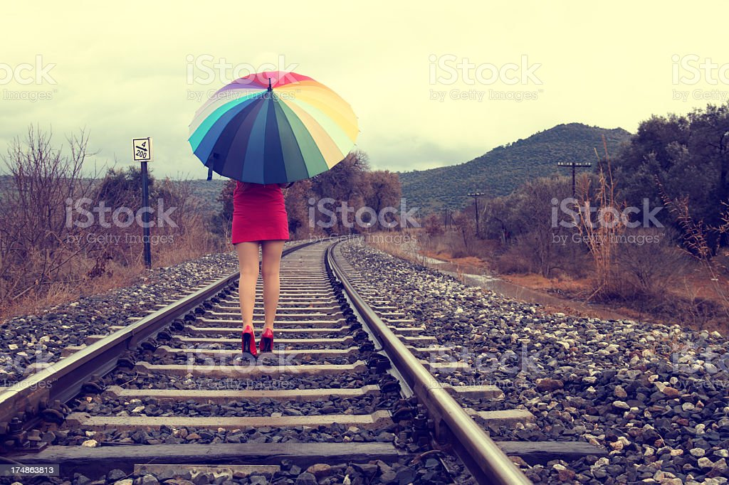 Woman in red walking on railroad with colorful umbrella royalty-free stock photo