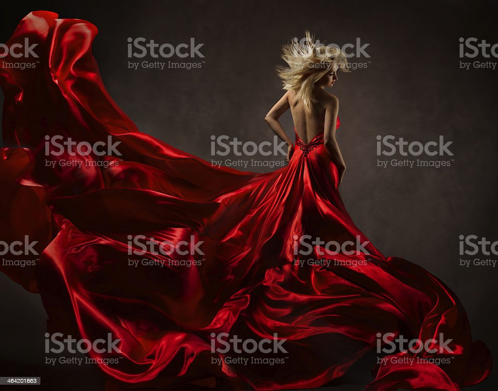 Woman in red waving dress dancing with flying fabric stock photo