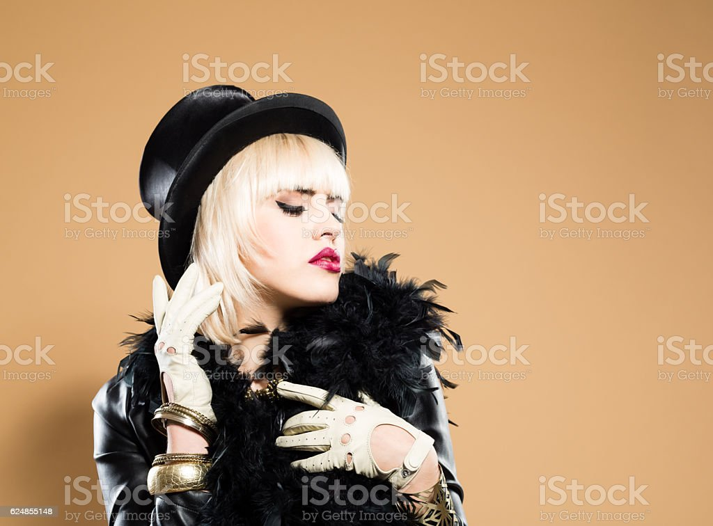 Woman in retro style costiume, wearing cylinder hat and boa stock photo