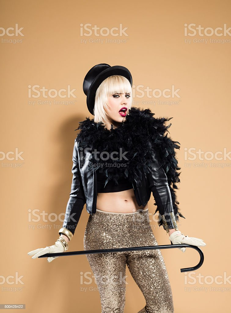 Woman in retro style outfit, wearing cylinder hat and boa stock photo