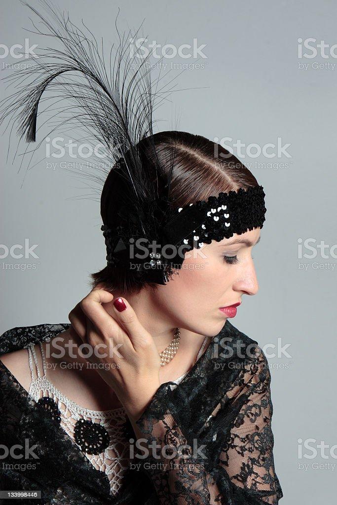 woman in retrow look of 1920s with feather hair band royalty-free stock photo