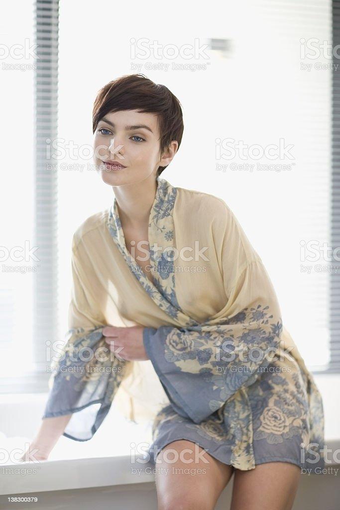 Woman in robe testing bathwater stock photo