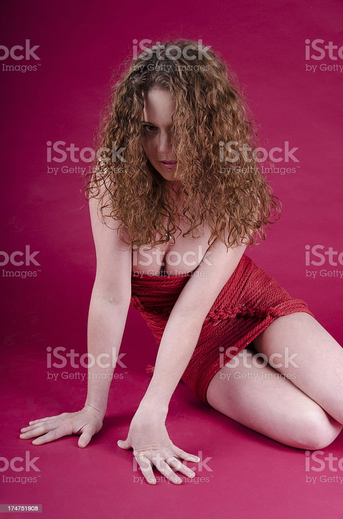 Woman in rope dress sitting on red background. royalty-free stock photo