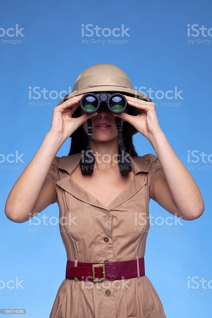 Woman in safari hat looking through binoculars royalty-free stock photo