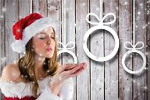 Woman in santa costume blowing snowflakes